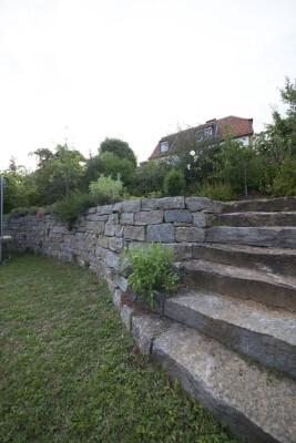 Garten Steinarbeiten Würzburg: Natursteinmauer und -Treppe in Kombination