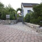 Eingangsbereich mit Naturstein und Rosenbogen